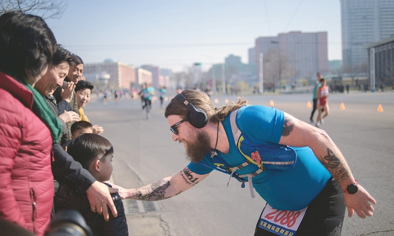 Pyongyang: A foreign competitor speaks to a child during the marathon.—AFP