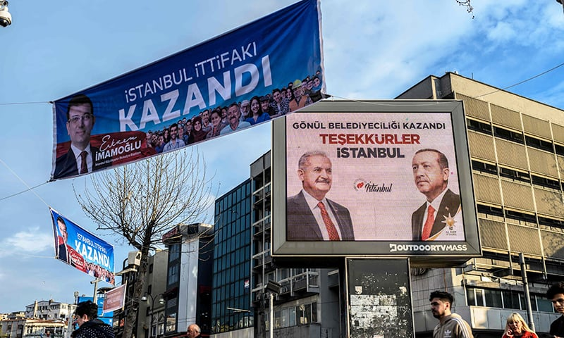"""A placard (L) with a picture of main opposition Republican People's Party (CHP) mayoral candidate Ekrem Imamoglu reading """"Istanbul alliance has won"""" next to the billboard (R) reading """"Municipality has been won with heart, Thank you Istanbul"""" and portraying AKP ruling party mayor candidate Binali Yildirim and President Recep Tayyip Erdogan are displayed in Kadikoy District of Istanbul on April 9. — Reuters"""