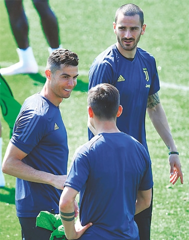 TURIN: Juventus players Cristiano Ronaldo (L) and Giorgio Chiellini (top) seen during a practice session on the eve of their Champions League quarter-final against Ajax.—AP