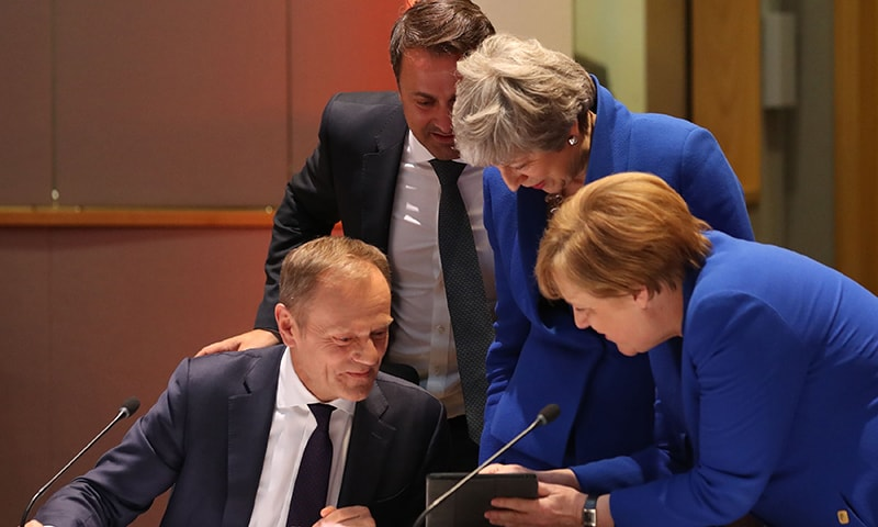 European Council President Donald Tusk (L), Luxembourg's Prime minister Xavier Bettel (C-L), Britain's Prime minister Theresa May (C-R) and Germany's Chancellor Angela Merkel (R) look at a tablet ahead of a European Council meeting on Brexit at The Europa Building. ─ AFP