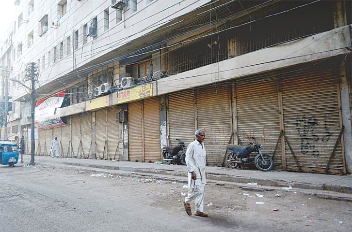 A MAN walks past the shops shuttered in protest over the murder of a trader on Wednesday.—PPI