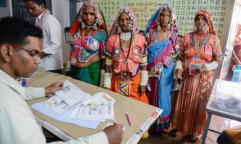 An official checks the names of Indian lambadi tribeswomen at a polling station during India's general election at Pedda Shapur village on the outskirts of Hyderabad on April 11, 2019. ─ AFP