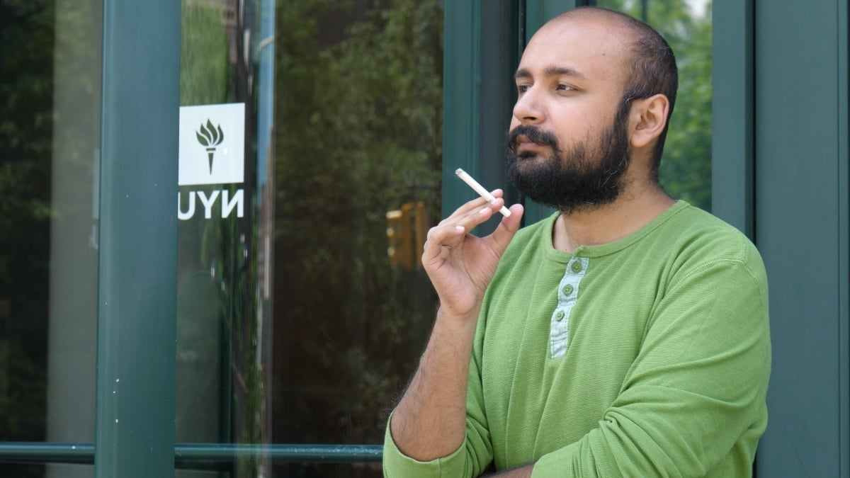 Filmmaker Fahad Naveed smokes outside a NYU campus building. — Publicity