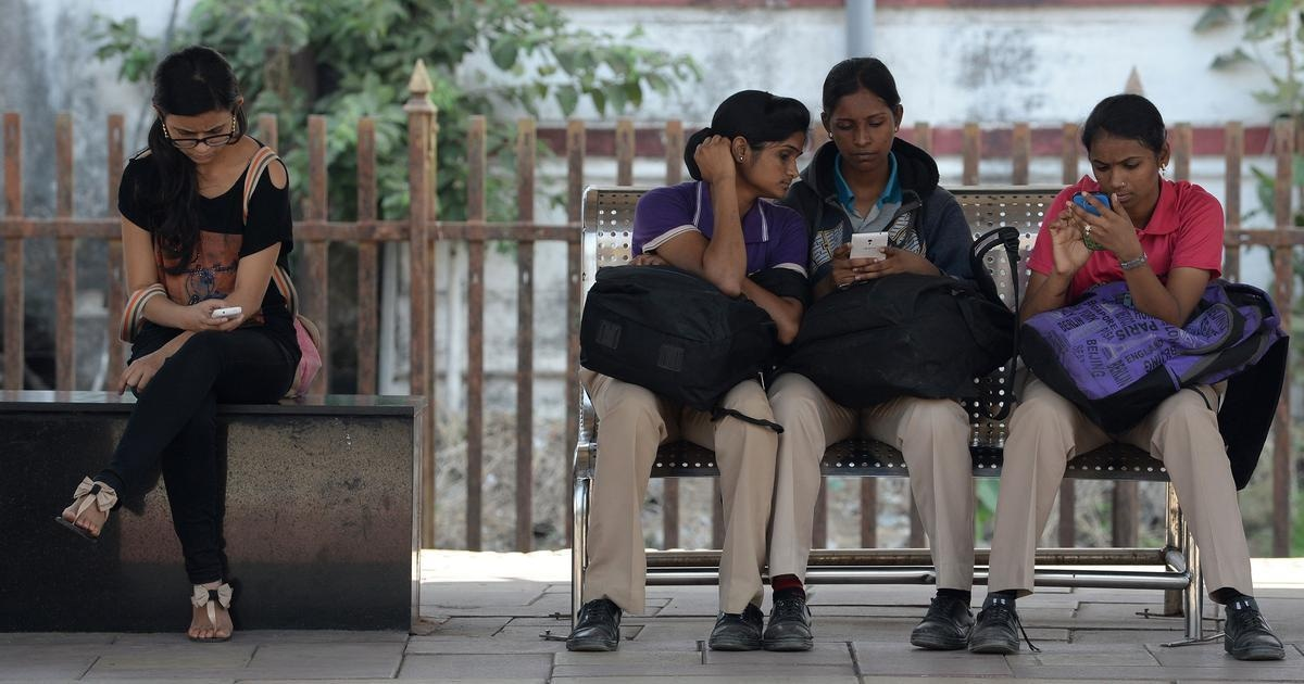 Indian women check their mobile telephones at a free Wi-Fi Internet zone in Mumbai on | Indranil Mukherjee/AFP