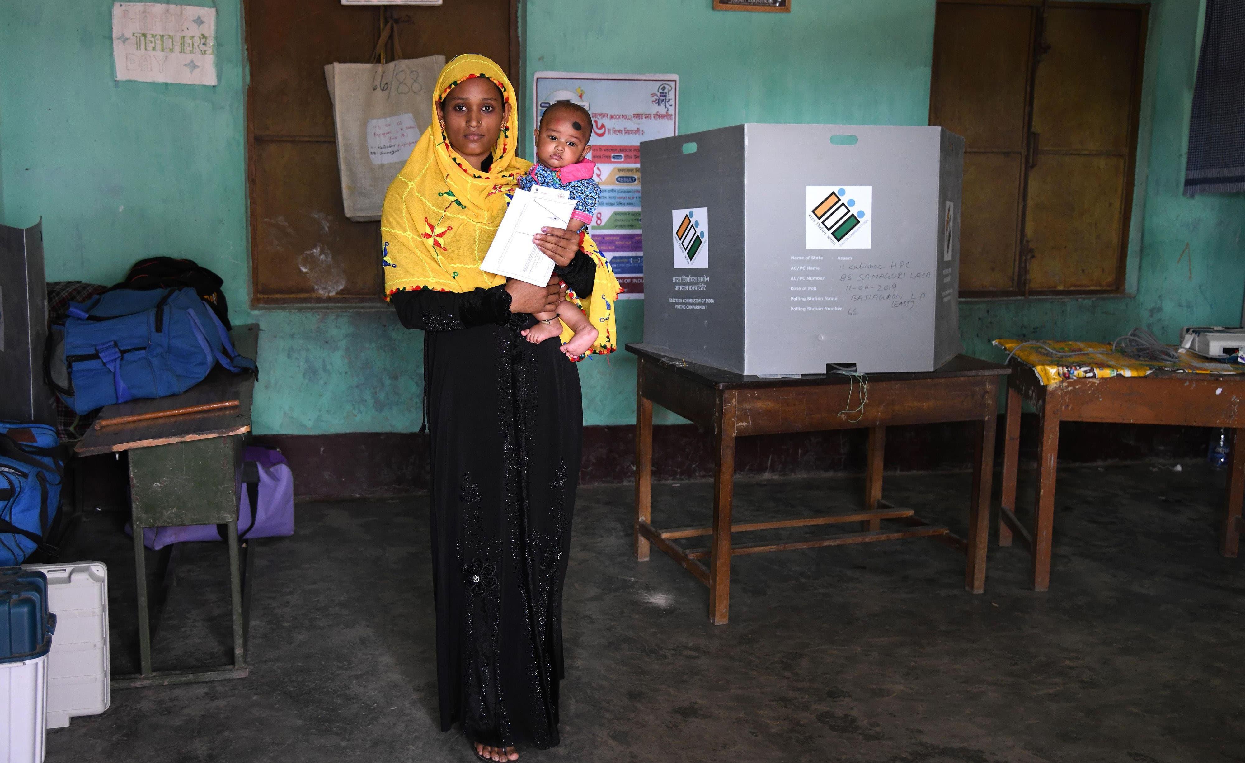 گوہاٹی کے قریب گاؤں پورندودام سے تعلق رکھنے والی خاتون بھی  اپنا حق رائے دہی استعمال کرنے کے لیے  بچے کے ہمراہ پولنگ اسٹیشن پہنچی —فوٹو/ اے ایف پی