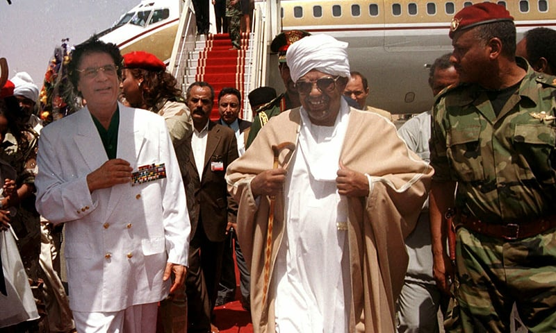 Libyan leader Moammar Gadhafi , left, is greeted by President Omar El-Bashir, center, upon his arrival in Khartoum for a two-day visit to Sudan. ─ AP