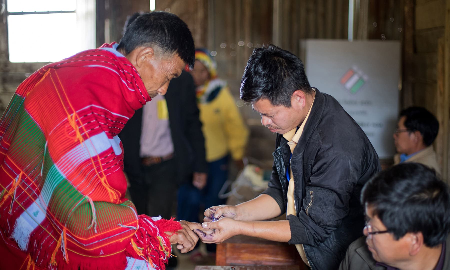 A polling officer puts an ink mark on an Indian tribal voter's finger before he casts his vote for the first phase of India's general election in Ukhrul district in the northeastern state of Manipur on April 11, 2019. — AFP