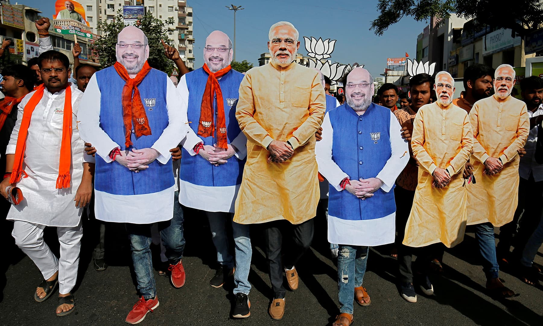 Supporter of India's ruling BJP wearing cut-outs of Prime Minister Narendra Modi and the party president Amit Shah walk during an election campaign in Ahmedabad, India, April 11, 2019. — Reuters