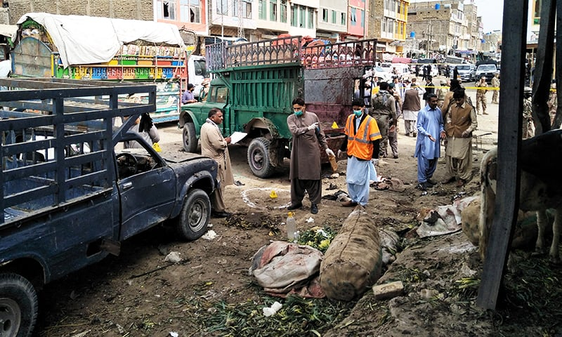 Members of the bomb disposal unit survey the site after a blast at a vegetable market in Quetta. ─ Reuters
