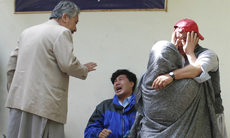 Family members of the blast victims comfort each other outside a mortuary in Quetta. ─ AP