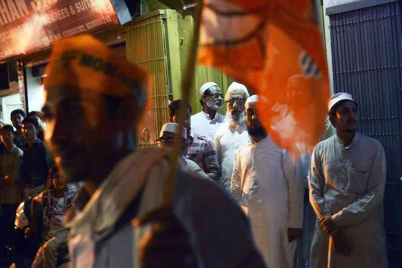 A group of Muslim men stand on the side of a street as they wait to see a car convoy carrying BJP candidate Narendra Modi in Varanasi on May 8, 2014. (Photo credit: Roberto Schmidt/AFP)