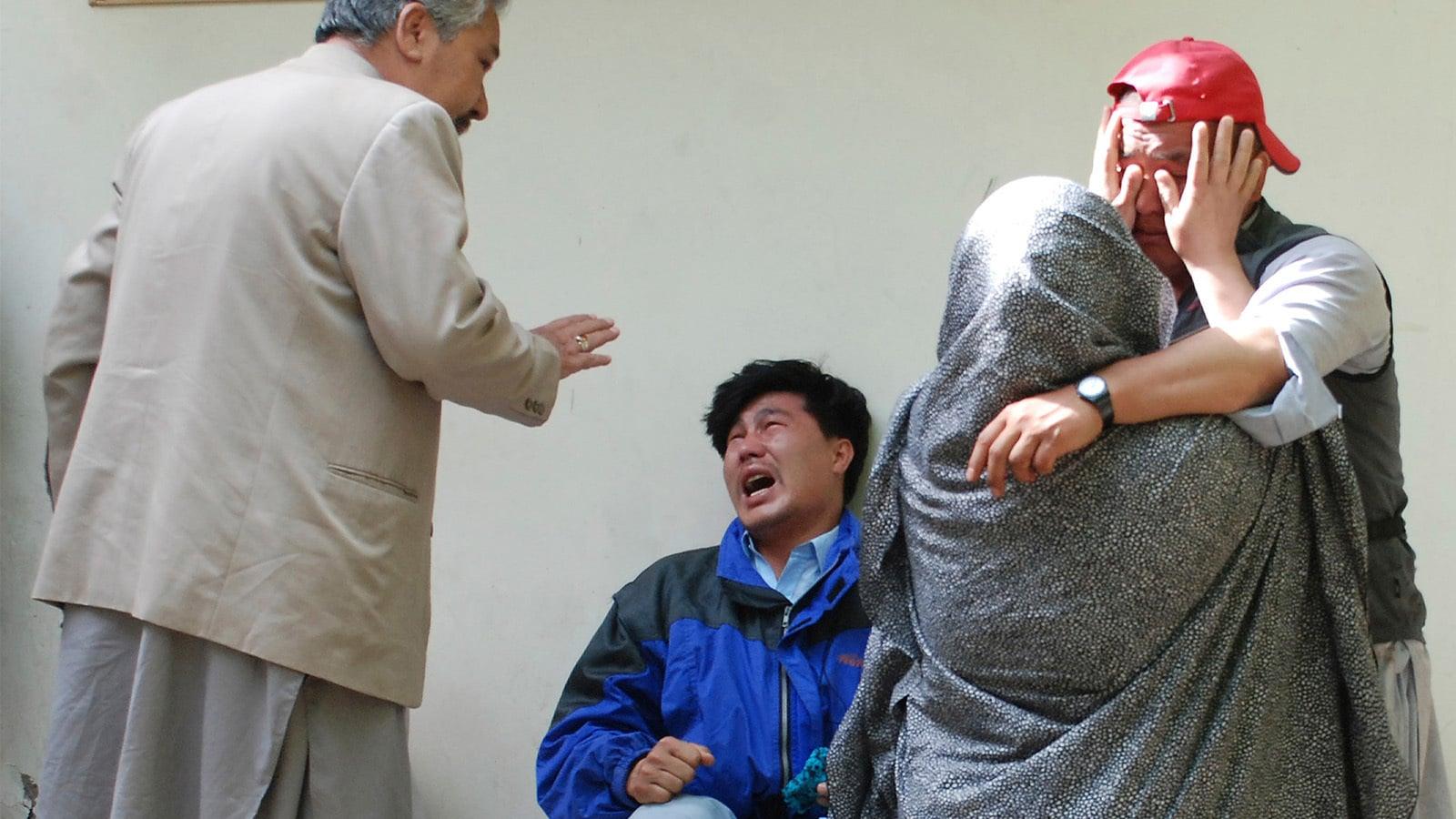 جان بحق افراد کے اہلِ خانہ شدت غم سے نڈھال ایک دوسرے کو تسلی دیتے ہوئے—تصویر:اے پی