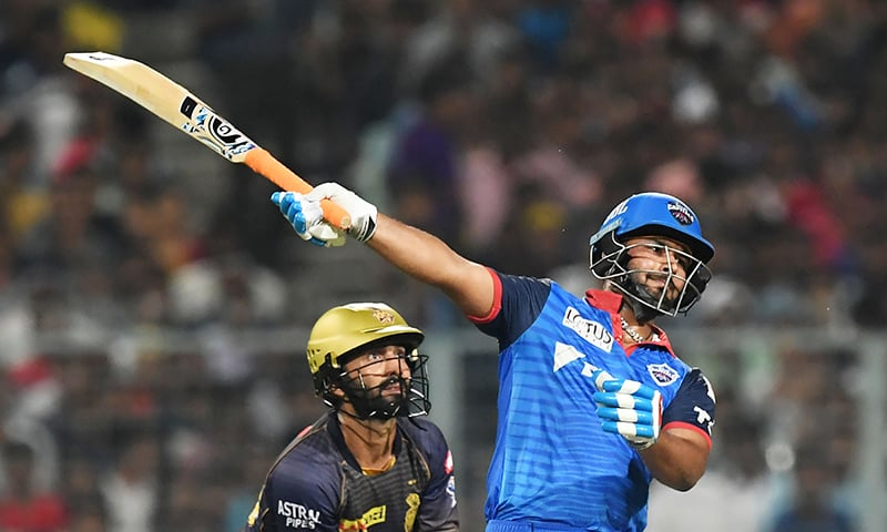Delhi Capitals' Rishabh Pant plays a shot as Kolkata Knight Riders' Dinesh Karthik looks on, during the Indian Premier League (IPL) Twenty 20 cricket match between  Kolkata Knight Riders and Delhi Capitals at the Eden Gardens Cricket Stadium, in Kolkata, on April 12, 2019. — AFP