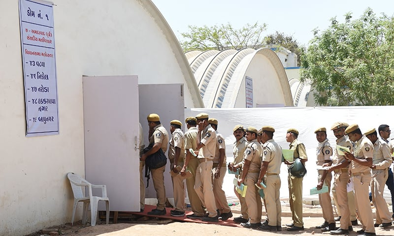 Gujarat police personnel queue before casting their votes at a polling station at the Ahmedabad Police Headquarters in Ahmedabad on April 12, 2019. — AFP
