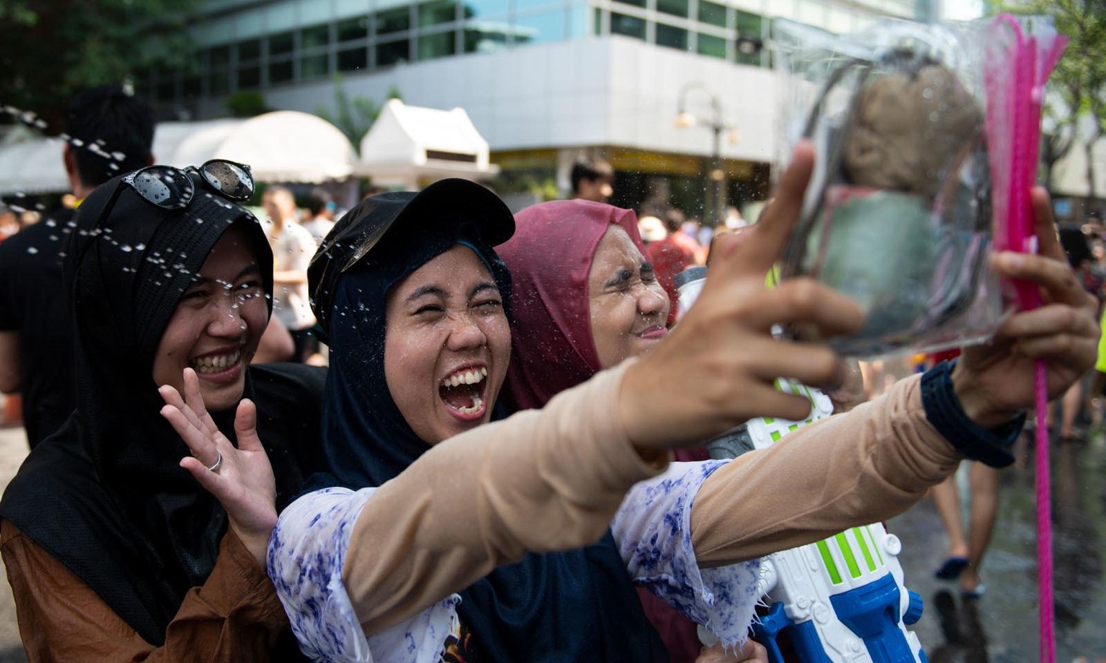 تقریب میں شریک لڑکیاں سیلفی لے کر لمحات کو یادگار بنا رہی ہیں—فوٹو: اے ایف پی