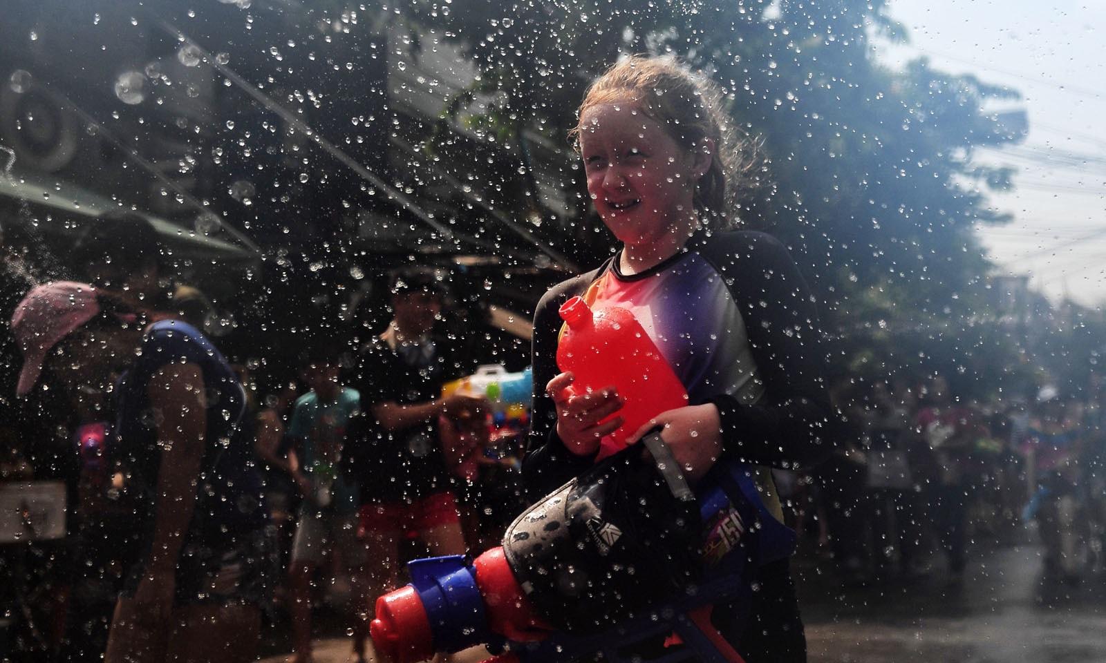ایک تھائی بچی واٹر گن اٹھائے آگے بڑھ رہی ہے—فوٹو: اے ایف پی
