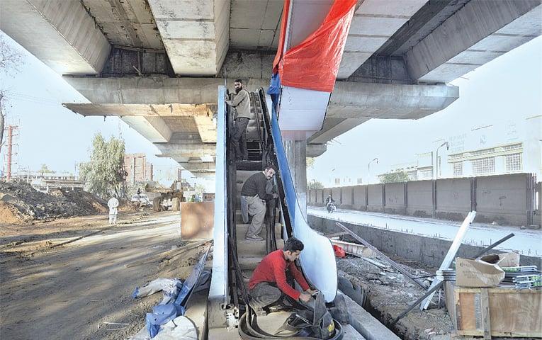 Workers install an escalator at a BRT station near Peshawar Cantt railway station | Shahbaz Butt/White Star