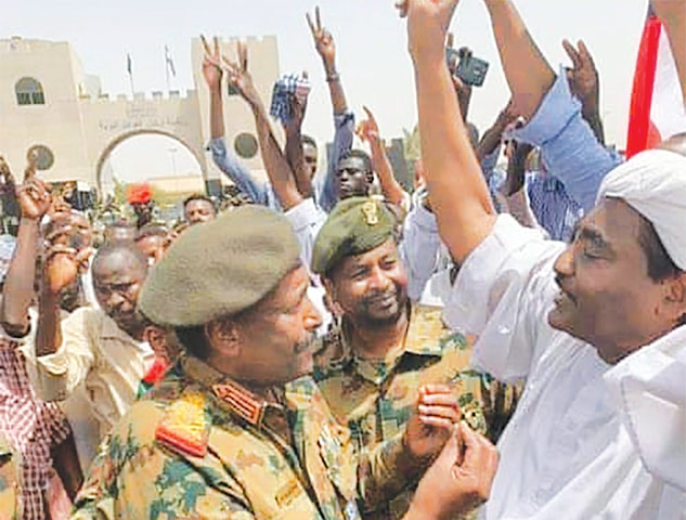 Khartoum: Lieutenant General Abdel Fattah al-Burhan, the new chief of the military council, speaking with demonstrators outside the army headquarters in the capital.—AFP