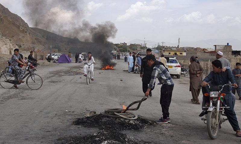 مظاہرین نے احتجاج کرتے ہوئے ٹائر جلائے اور سڑکوں کو بلاک کردیا— فوٹو: اے پی