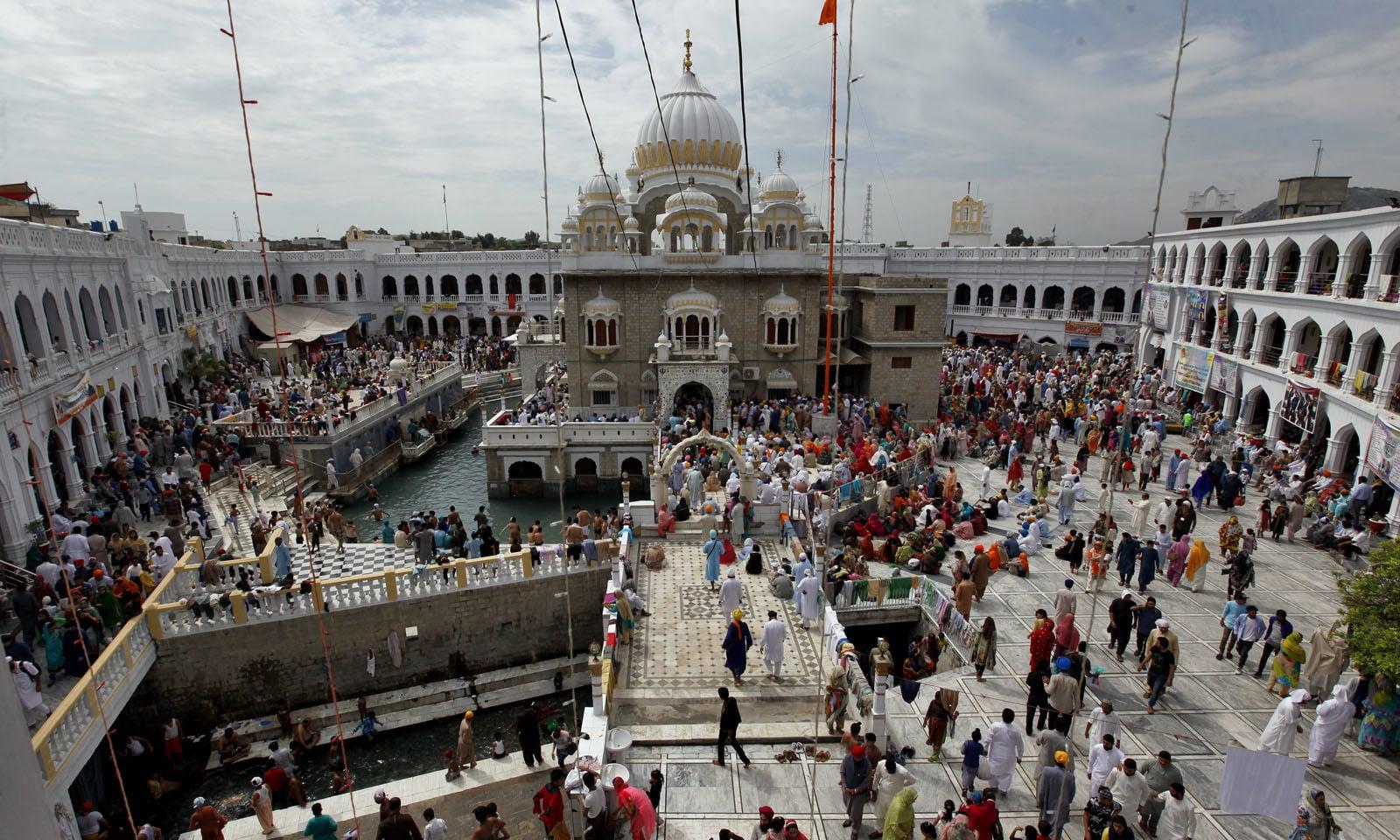 گرودوارہ پنجہ صاحب کے مقدس تالاب میں عقیدت مند غسل کرتے ہیں—فوٹو: اے پی