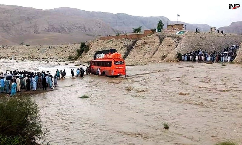 PEOPLE are being taken out from a bus that was stuck in floodwaters on a highway near Quetta on Sunday. Heavy rains in different parts of Balochistan in the past two days have caused flash floods and inundation of highways. — INP