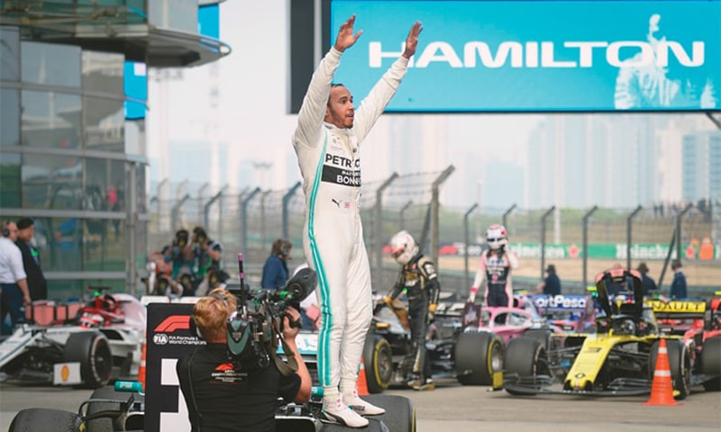 SHANGHAI: Mercedes' Lewis Hamilton celebrates on his car after winning the Chinese F1 Grand Prix on Sunday. — AFP
