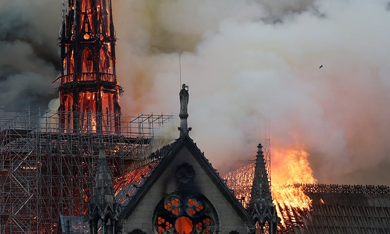 Smoke billows near scaffolding as fire engulfs the spire of Notre Dame Cathedral in Paris. ─ Reuters