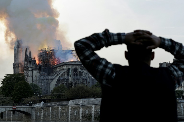 Anxious passers-by watched the landmark cathedral burn on Monday. — AFP