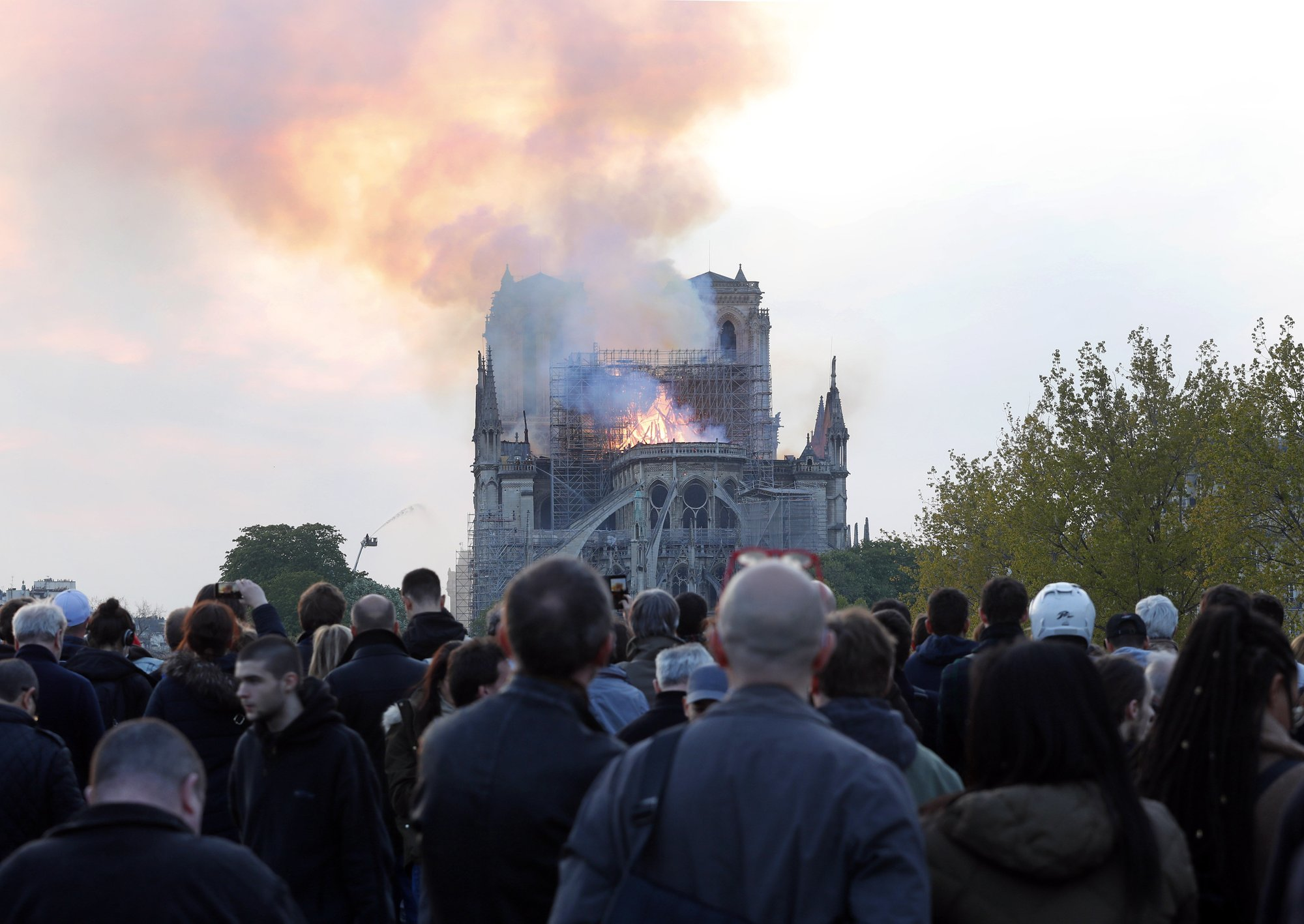 People watch as flames and smoke rise from Notre-Dame cathedral as it burns in Paris. — AP