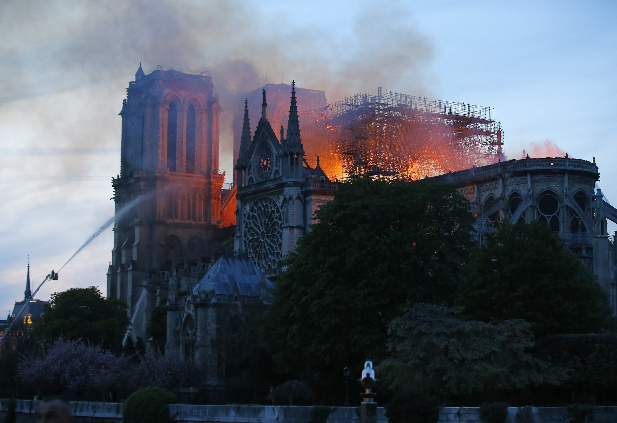 A firefighter tackles the blaze as flames and smoke rise from Notre-Dame cathedral as it burns in Paris. — AP