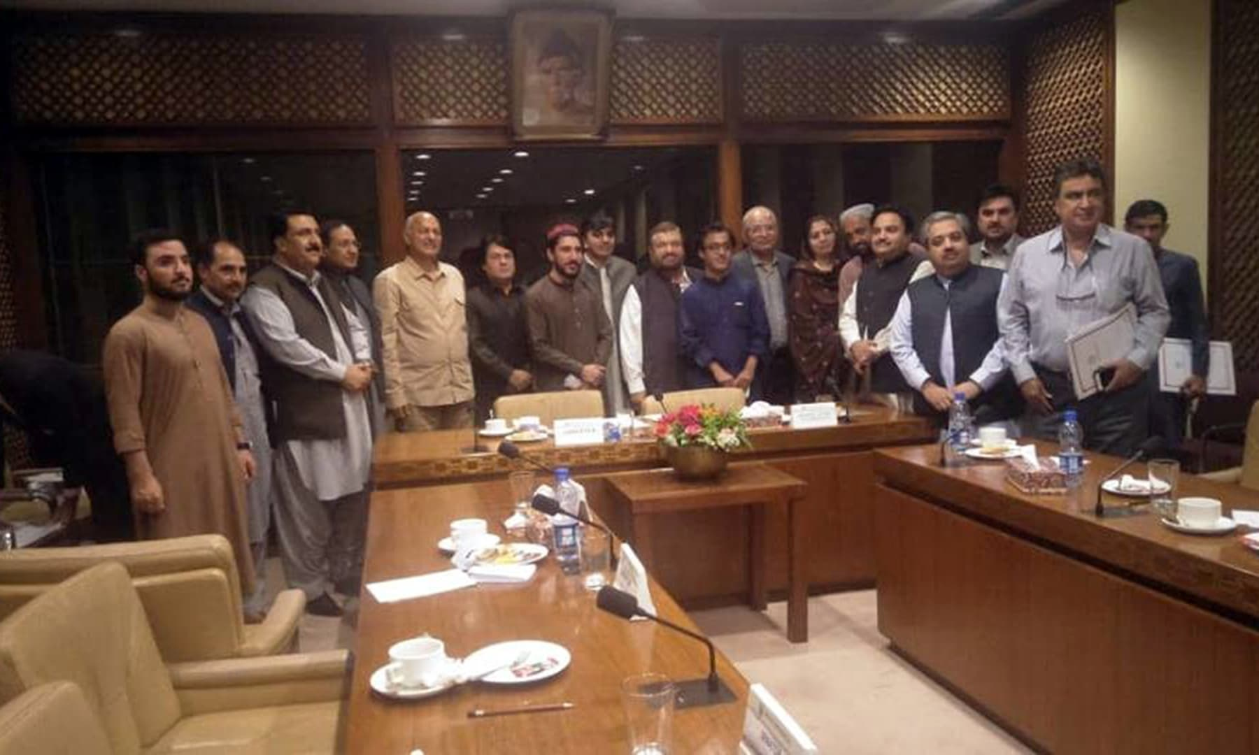 "Senators and PTM leadership are seen standing together under the portrait of Quaid-e-Azam, on what the Senate committee termed was ""a historic day"", April 16. — PTM"