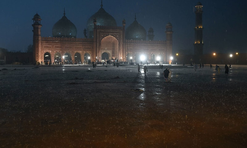People arrive to pray at Badshahi Mosque during heavy rain in Lahore on April 16, 2019. — AFP
