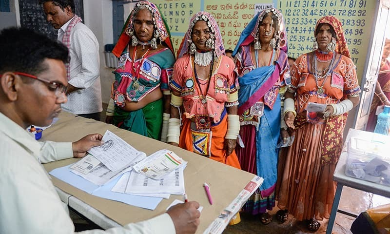 In this file photo, an official checks the names of Indian lambadi tribeswomen at a polling station during India's general election at Pedda Shapur village on the outskirts of Hyderabad on April 11, 2019. ─ AFP