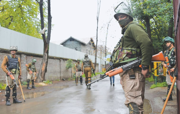 SRINAGAR: Indian paramilitary personnel stand guard outside a polling station on Wednesday.—AFP