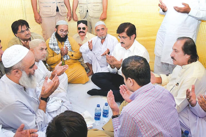 Sindh Chief Minister Syed Murad Ali Shah offering Fateha after condoling with the father of the child killed by police fire. — APP