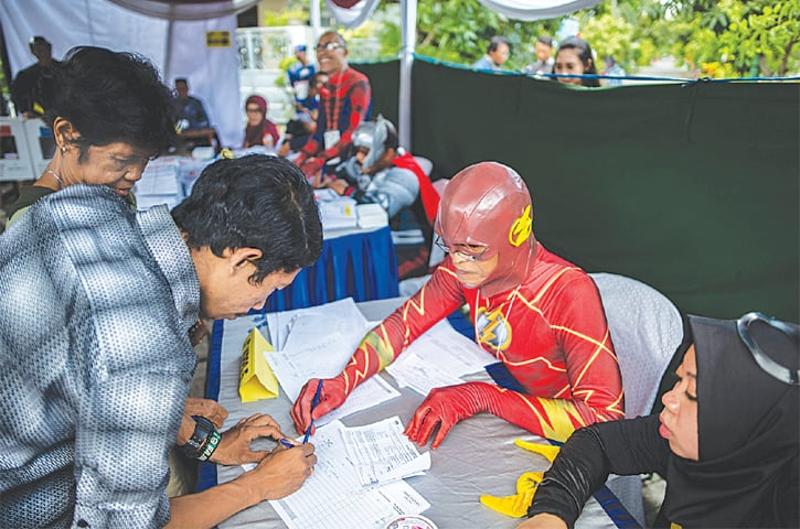 SURABAYA (Indonesia): Election workers dressed in superhero costumes register voters at a polling station on Wednesday. Indonesia held one of the world's biggest one-day polls, pitting President Joko Widodo against ex-general Prabowo Subianto in a race to lead the Muslim-majority nation. Mr Widodo won a second five-year term in a victory for moderation over the nationalistic rhetoric of Mr Subianto.—AFP