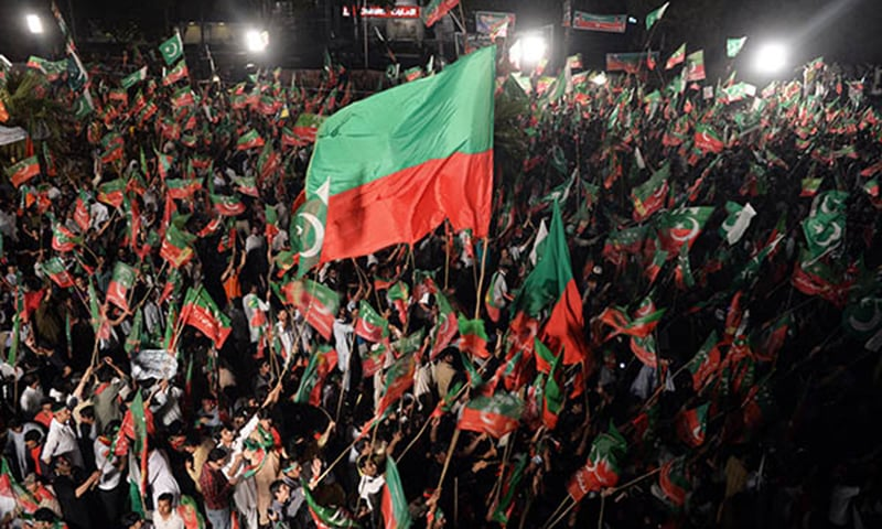 PTI workers wave party flags during a rally. — AFP/File