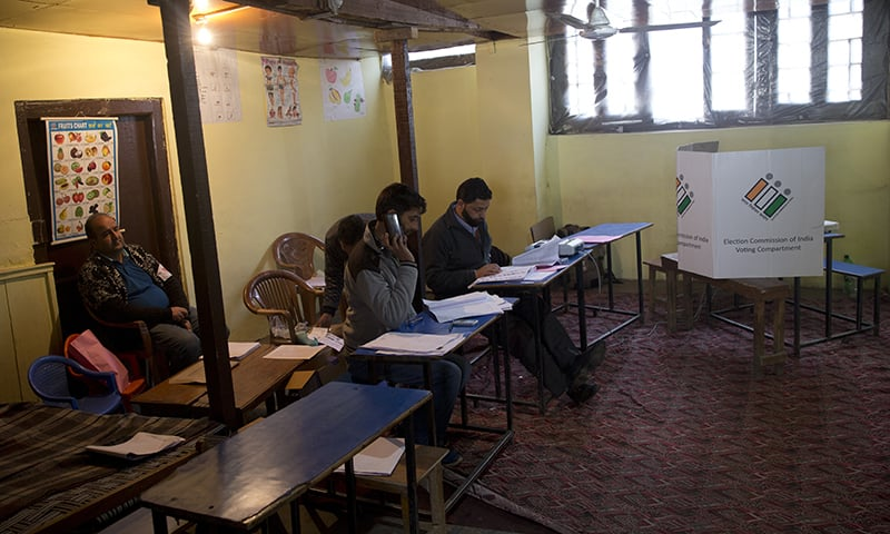 Election officers sit inside an empty polling station during the second phase of India's general elections, in Srinagar, ─ AP