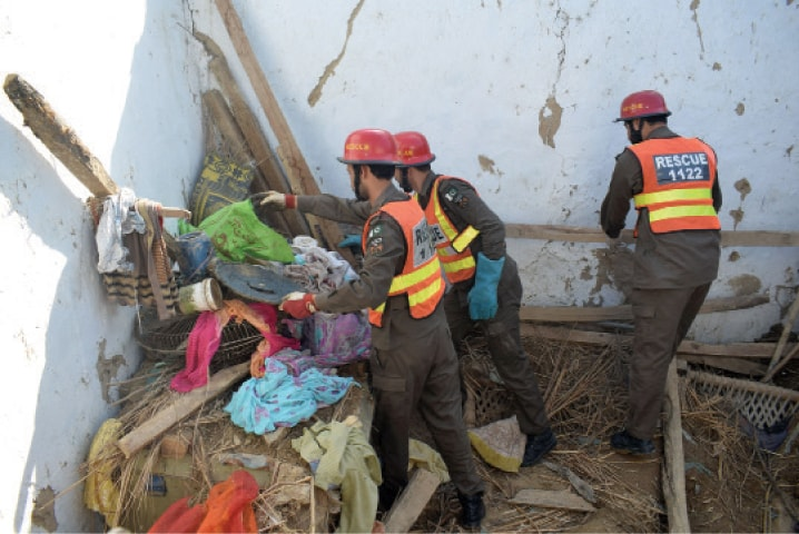 Rescue workers remove household items from the debris after the roof of a house collapsed in Behram Dheri area of Charsadda on Thursday. — White Star