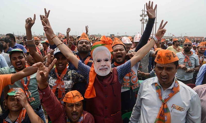 In this file photo taken on April 3, 2019 Indian supporters of the Bharatiya Janata Party (BJP) shout slogans surrounding a man wearing a mask of Indian Prime Minister Narendra Modi at a campaign rally ahead of the national elections in Siliguri. ─ AFP