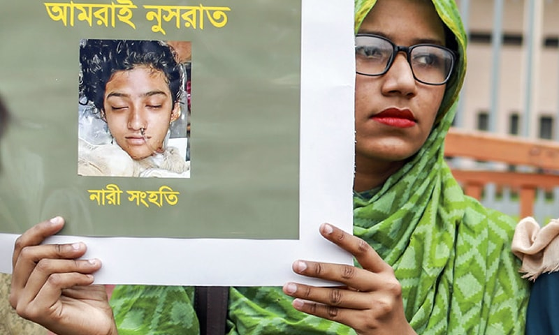 In this photo taken on April 12, a Bangladeshi woman holds a placard with a photograph of schoolgirl Nusrat Jahan Rafi at a protest in Dhaka. — AFP