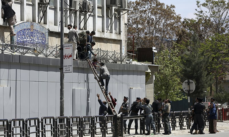 Afghan security personnel rescue men and children from the information and culture ministry after an attack near to the Telecommunication Ministry in Kabul. — the AP