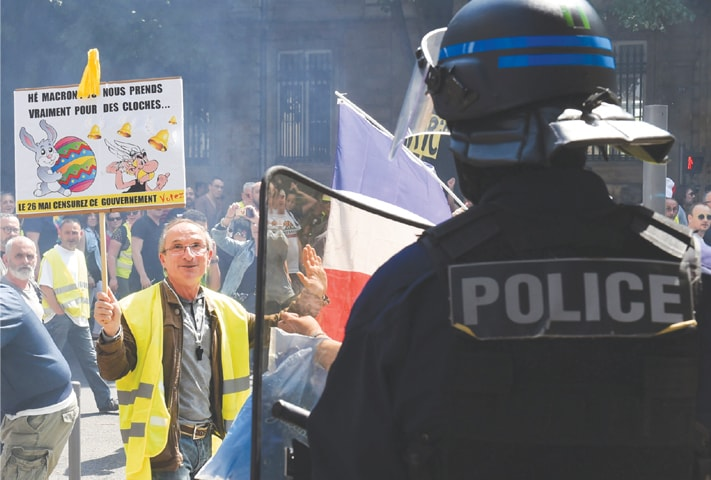 Bordeaux: A protester gestures to police as he holds a placard during an anti-government demonstration called by the  'yellow vests' movement on Saturday.—AFP