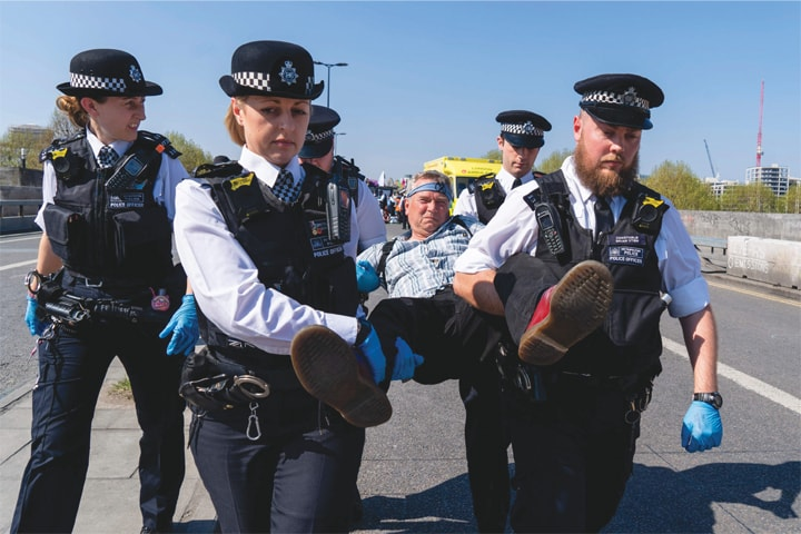 LONDON: Police officers arrest and carry away a climate change activist from a demonstration blocking Waterloo Bridge on Saturday.—AFP
