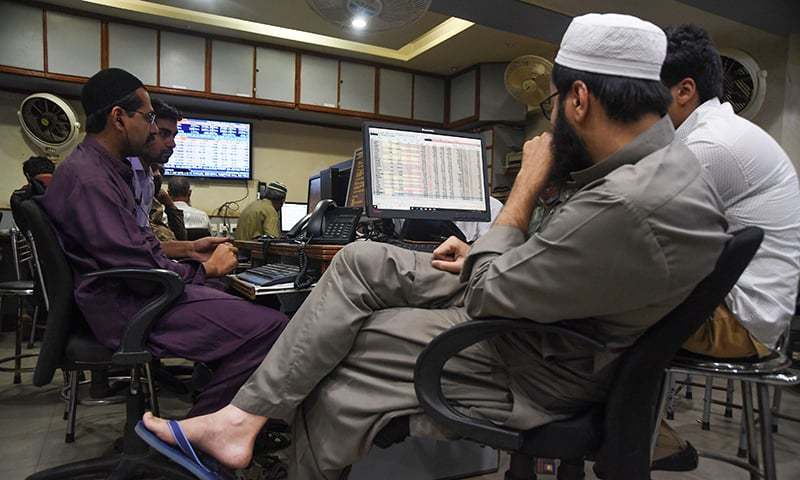 Stockbrokers monitor share prices during a trading session at the Pakistan Stock Exchange (PSX) in Karachi on April 17. ─ AFP/File