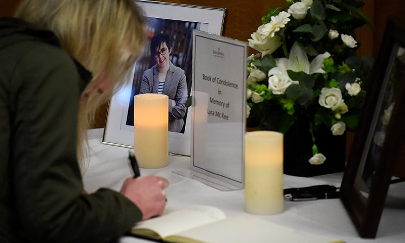 A woman signs a book of condolences in the Guildhall for the 29-year-old journalist Lyra McKee who was shot dead in Londonderry, Northern Ireland. ─ Reuters