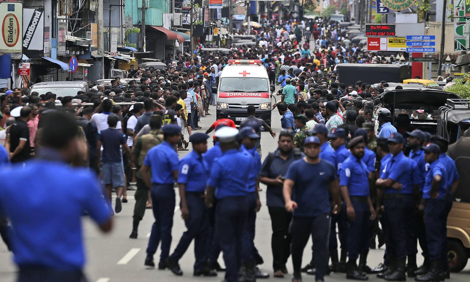 Sri Lankan police officers clear the road as an ambulance drives through carrying victims of the church blast in Colombo. ─ AP