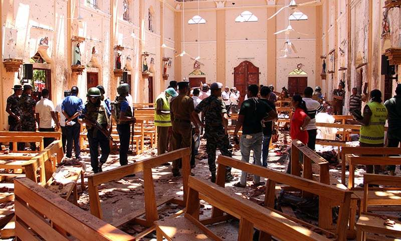 Sri Lankan security personnel walk through debris following an explosion in St Sebastian's Church in Negombo, north of the capital Colombo, on Sunday. — AFP