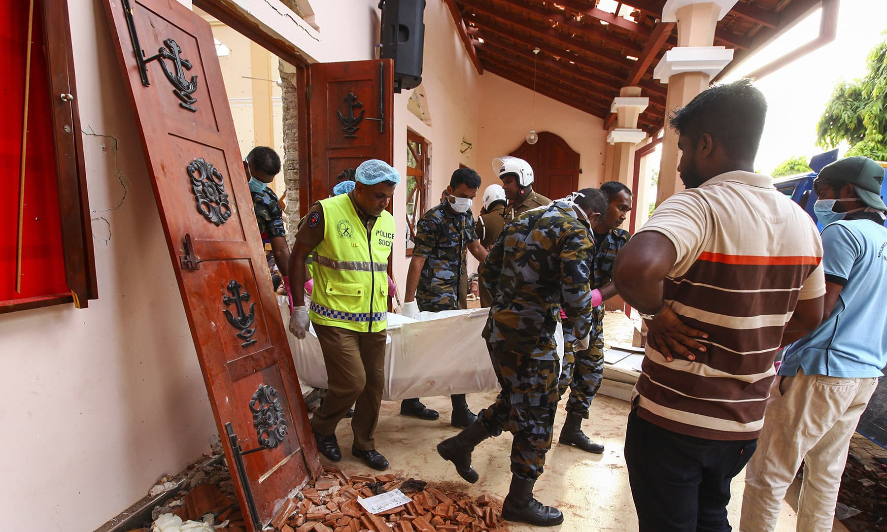 Sri Lankans carry a dead body at St. Sebastian's Church damaged in a blast in Negombo. — AP