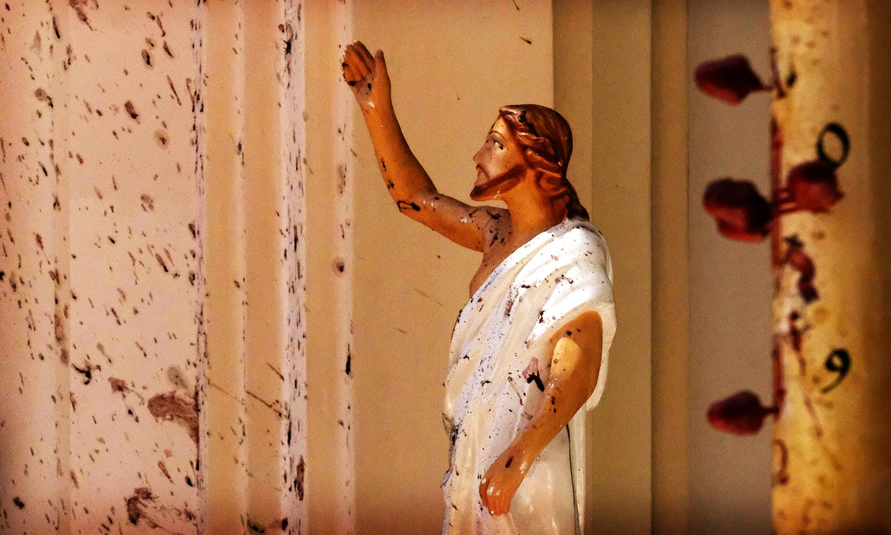 Blood stains are seen on the wall and on a Jesus Christ statue at the St Sebastian's Church after a blast in Negombo. — AP